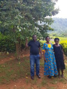 Image of Victor and Justine (middle), shaded by Guava planted at the compound